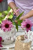 Woman arranging summer bouquet with echinacea