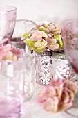 Empty wine glasses and pink hydrangeas in silver beaker