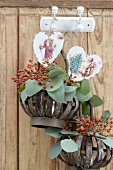 Twigs of rosehips and leaves in baskets and hearts with Christmas motifs hanging from hooks on wooden wall