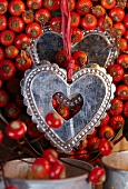 Small silver hearts hanging on red ribbons against rosehips