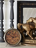 Antique alarm clock and gilt horse ornament in front of mirror