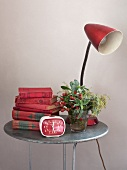 Old books, alarm clock, flowers and fifties-style table lamp on side table