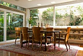 Dining table and armchairs in traditional Mediterranean style on classic Oriental rug in front of large windows running round two sides of room
