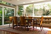 Esstisch und Armlehnstühle im traditionell südländischen Stil auf klassischem Orientteppich vor umlaufender Fensterfront