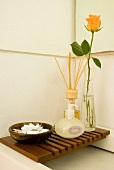 Soap, fragrance sticks and cut rose on wooden slatted rack over shallow washbasin
