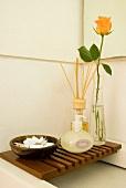 Holzrost als Ablage für Seife, Duftstäbchen und Schnittrose über einem Flachwaschbecken