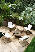Cantilever chairs with canvas seats and original tree trunk table on pale stone flagged floor surrounded by tropical garden vegetation