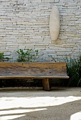 Rustic bench made from hollowed-out tree trunk against stone wall on sunny terrace