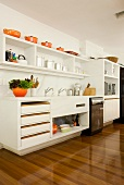 Pans and casseroles in cheerful orange bring colour to white modern kitchen with glossy parquet flooring