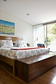 Double bed with floral bed linen and wide trunk of exotic wood in bedroom with open sliding door