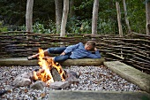 Boy lying on log bench next to bonfire
