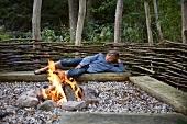 Junge liegt auf Holzstamm beim Lagerfeuer