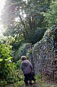 Boy pushing wheelbarrow next to garden wall