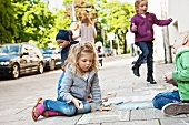 Children drawing with chalk on pavement