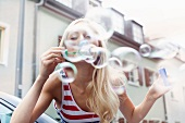 Blonde woman blowing soap bubbles