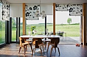 Dining set with 50s-style wooden chairs in front of panoramic windows with partially lowered blinds