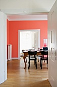 View through open double doors of table and dark wood chairs in front of salmon pink wall