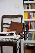 Apricot on stack of books and brown handbag on antique chair against wall next to open doorway showing view of bookcase beyond