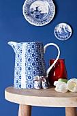 Stillleben mit Kannen auf Holztisch, Teller mit Holland-Motiven als Wanddeko
