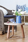 Blue jug and tulips on side table, cushions on wicker chair and scatter cushions on low storage bench