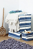 Blue and white laundry basket with lid and small storage basket with rug in foreground