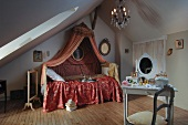 Romantic, feminine attic bedroom with Rococo canopy above bed and white-painted dressing table