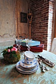 Stack of blue and white painted teacups and saucers next to silver cutlery and flower arrangement on vintage tablecloth in corner of rustic dining room