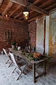 Kürbis und Blumenzweige auf rustikalem Holztisch und Klappstühle in scheunenartigem Raum