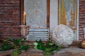Blätterzweig neben Steinkugel mit Pflanzenmuster und Kerzenständer mit brennender Kerze auf Tisch vor Holztür mit Paneelen und abblätternder Farbe