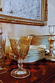 Ornamented wine glasses and gold-rimmed plates stacked on cabinet with chequerboard inlaid top