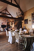 Enthusiasts' collection of antiques in salon of French country manor with romantic dinner table below rustic exposed roof structure