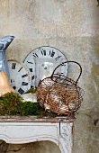 Old clock faces and wire basket of eggs on Rococo console table as romantic country house decoration