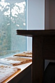 Animal skin cushions on bench in front of window element with fixed glass panel