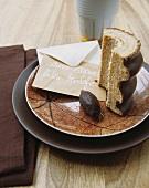 Aufgeschnittener Baumkuchen und beschriftetes Kuvert auf Schale mit Netzstruktur