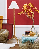 Tray of groceries on stool in front of standard lamp with white lampshade and wooden base and small tree against red-painted wall