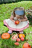 A blond girl with a Swiss apple, pears and pumpkins in the garden