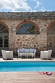 Terrace with white outdoor furniture and pool next to Mediterranean house
