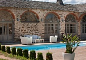 Topiary cypresses in front of pool and terrace with white seating in courtyard of Mediterranean residential complex