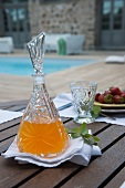 Set terrace table - refreshing drink in crystal carafe and glass on white linen napkin