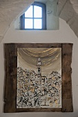 Picture of cityscape in rustic frame on wall below small lattice window