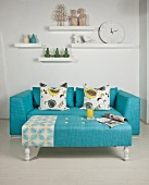 Ornaments on white shelving above turquoise couch and ottoman