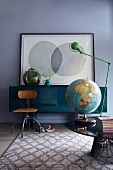 Room with globe and table lamp on round coffee table, old swivel chair and sideboard