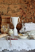 Glassware and crockery, vintage embroidered table linen and antique books on a table in front of a tapestry