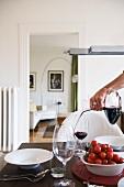 Frau giesst Rotwein in ein Glas am gedeckten Tisch