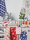 Colourful tea towels hanging on wall and lying on table