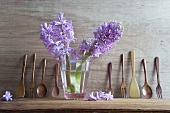 Hyacinths in glass of water and wooden utensils on shelf