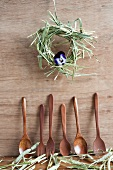 Wooden spoons and hay wreath with one viola flower hanging on wooden wall