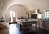 Traditional, simple kitchen with central island below barrel vaulted ceiling in Mediterranean country house