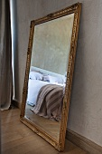 Mirror with traditional gilt frame on parquet floor leaning against wall