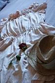 Rose und Strohhut auf ausgebreitetem Damenkleid dekoriert